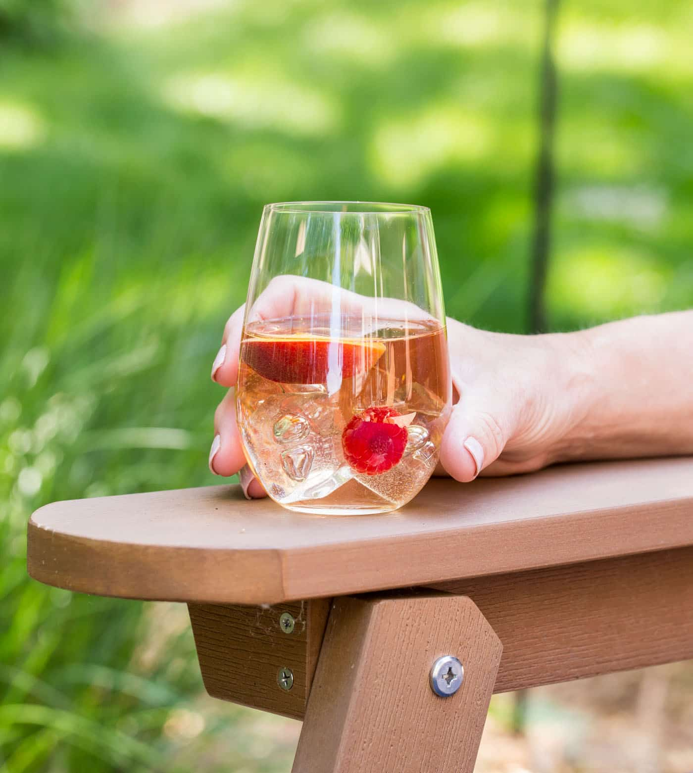 Glass of Peach Rosé Sangria with peach slices and raspberries floating in the glass. The glass is outside sitting on the arm of an adirondack chair.