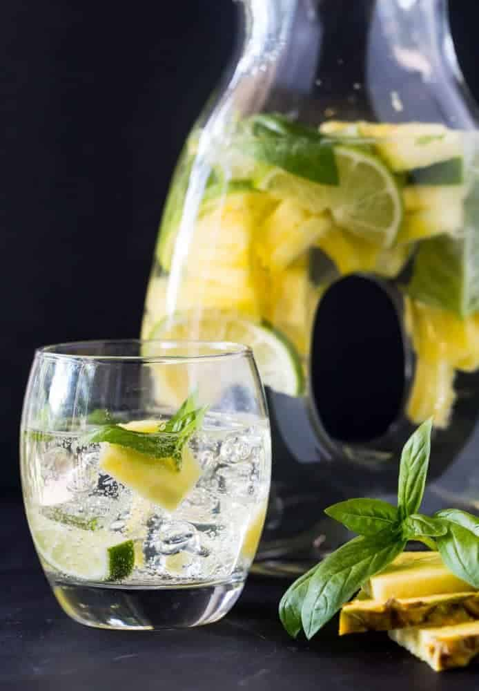 Picture of glass of Pineapple Sangria with pineapple slices, limes and basil. Also pictured is a pitcher of Pineapple Sangria in the background.