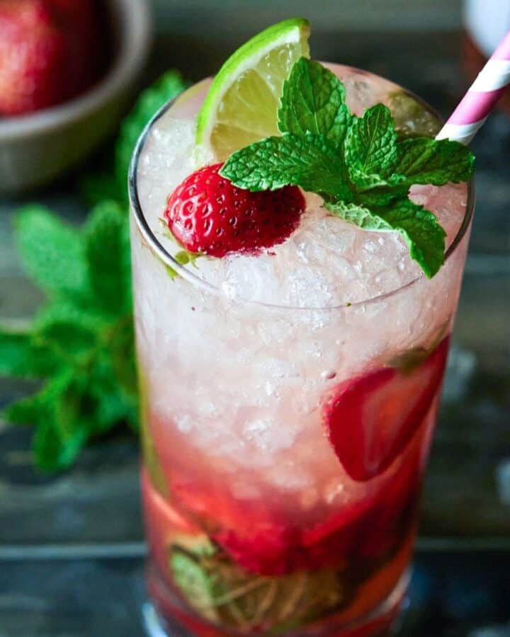 high ball glass filled with ice, strawberries and drink.