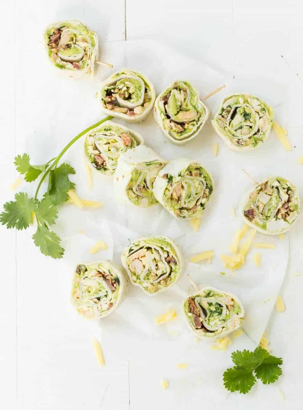 Avocado Bacon Pinwheel slices on parchment paper with cilantro sprig for garnish.