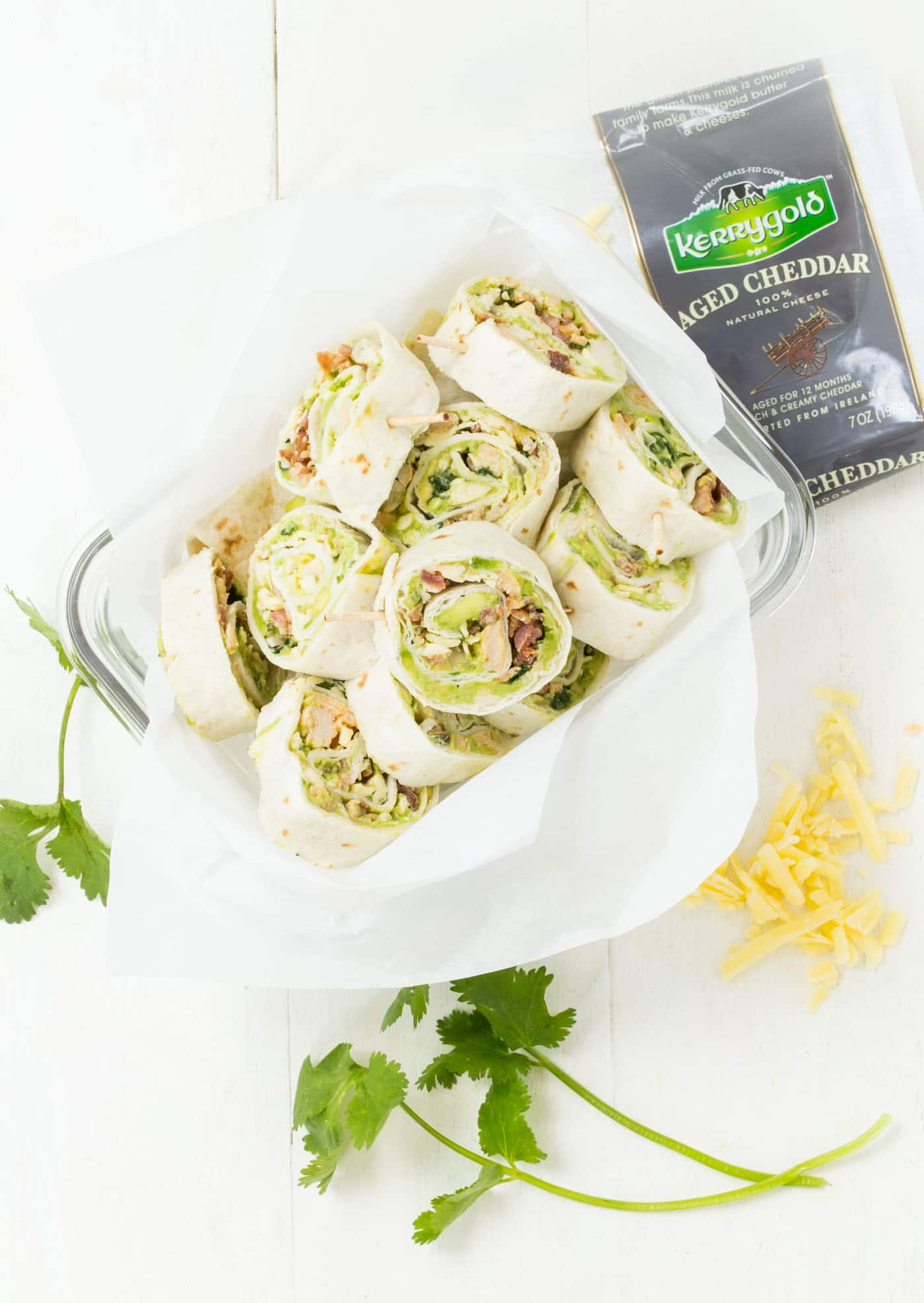 Avocado Bacon Pinwheels stacked in plastic bowl with shredded cheese and cilantro sprigs on the side.
