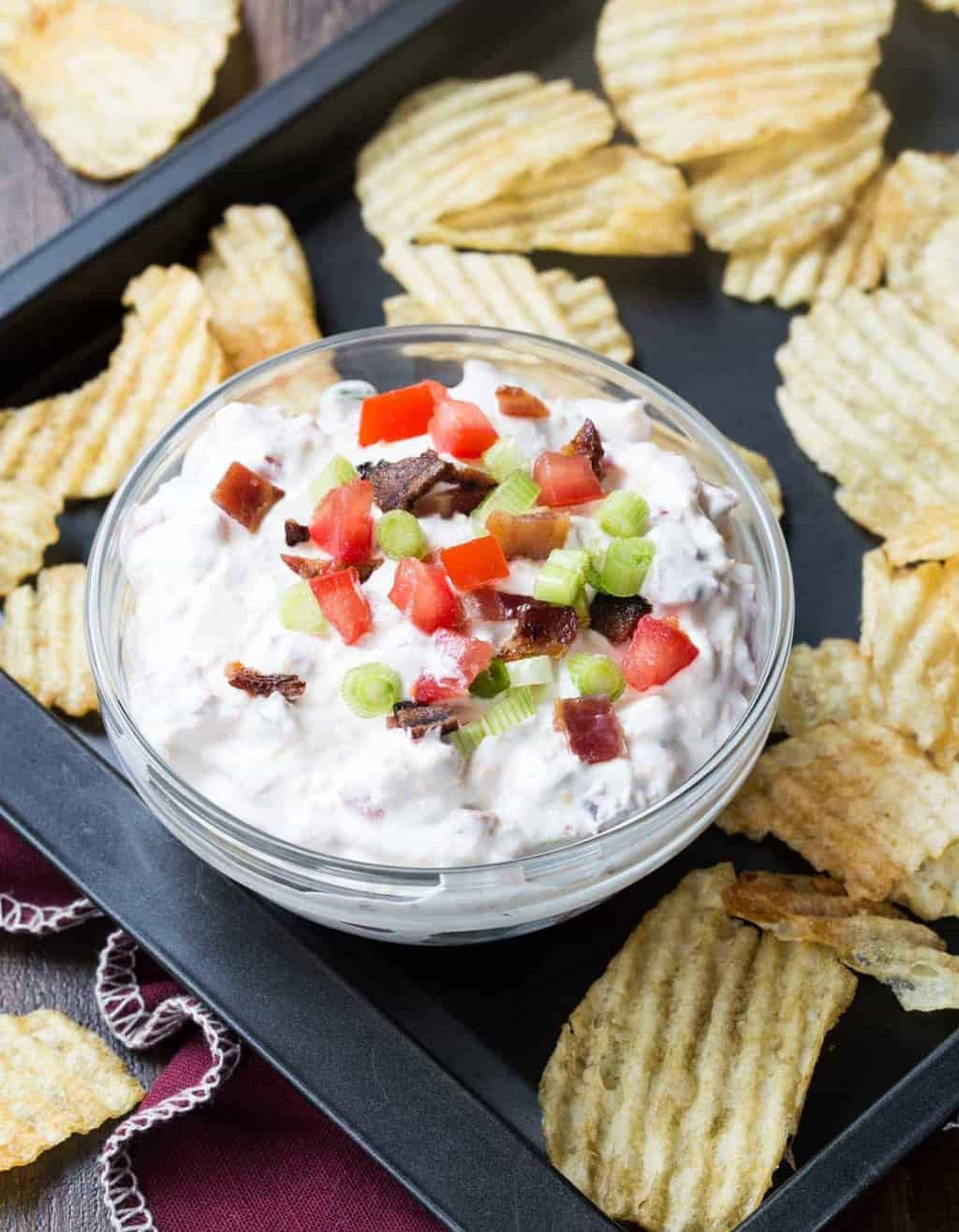 Small bowl of tomato bacon dip garnished with chopped tomato, bacon and green onions sitting on tray with potato chips scattered around.