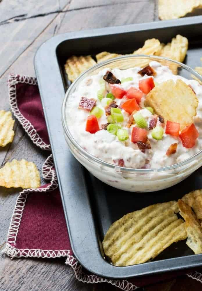 Small glass bowl of tomato bacon dip with a potato chip dipped in. Chopped tomato, bacon and green onion garnished on top of dip.