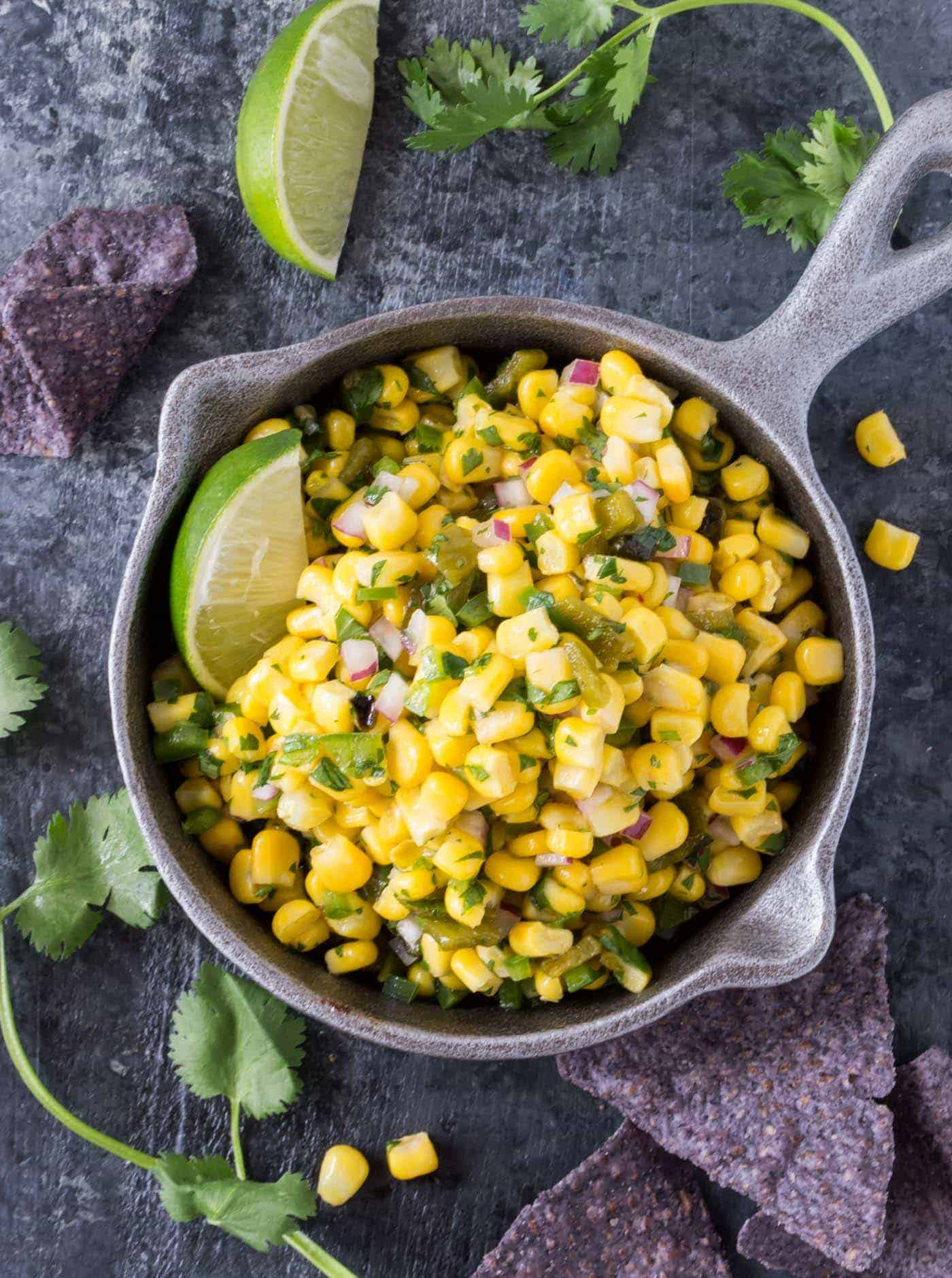 Bowl of Copycat Chipotle Corn Salsa recipe surrounded by chips, cilantro and lime wedges.