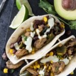 Two Corn and Mushroom Tacos with poblano peppers, avocado crema, salsa verde and avocado and lime slices.