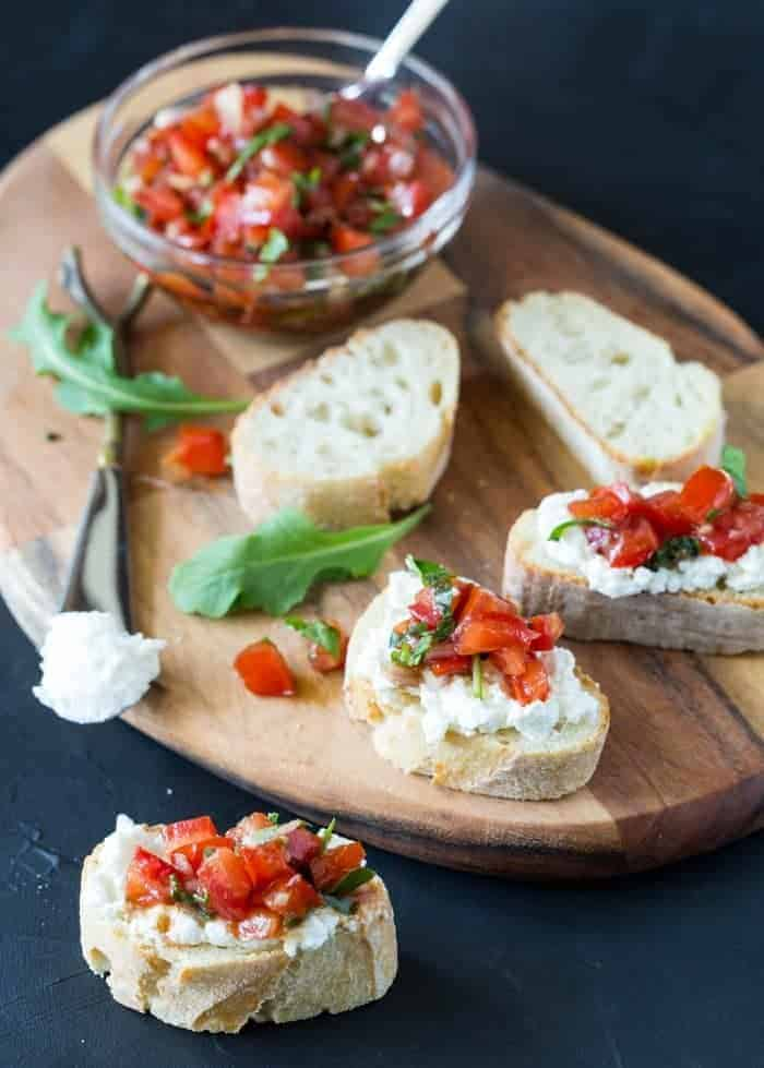 Baguette slices with Fresh Tomato Arugula Bruschetta on top of fresh ricotta cheese on bread board.