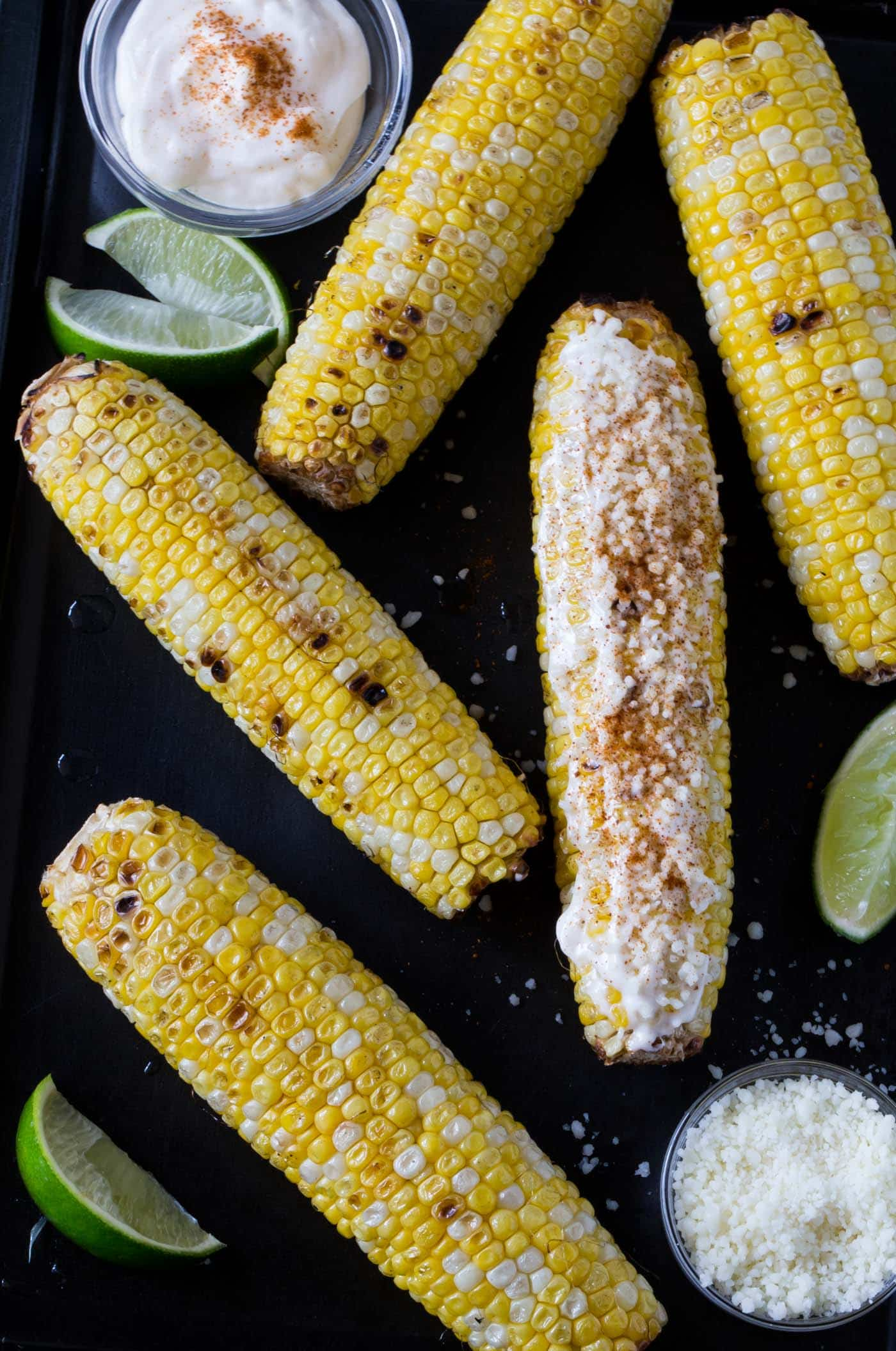 Mexican Grilled Corn with mayonnaise, lime wedges, cotija cheese and cayenne pepper on a sheet pan