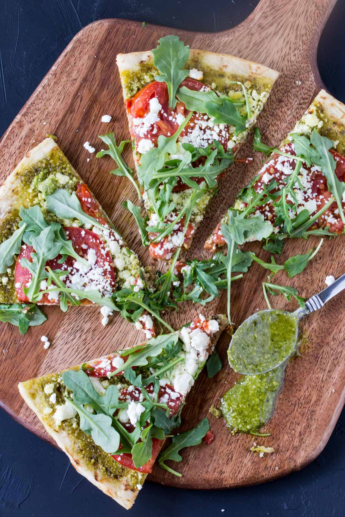 Wooden cutting board with three slices of Pesto Pizza with goat cheese, tomatoes and arugula.
