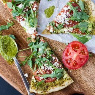 pesto pizza recipe on a wooden cutting board with tomatoes and fresh arugula