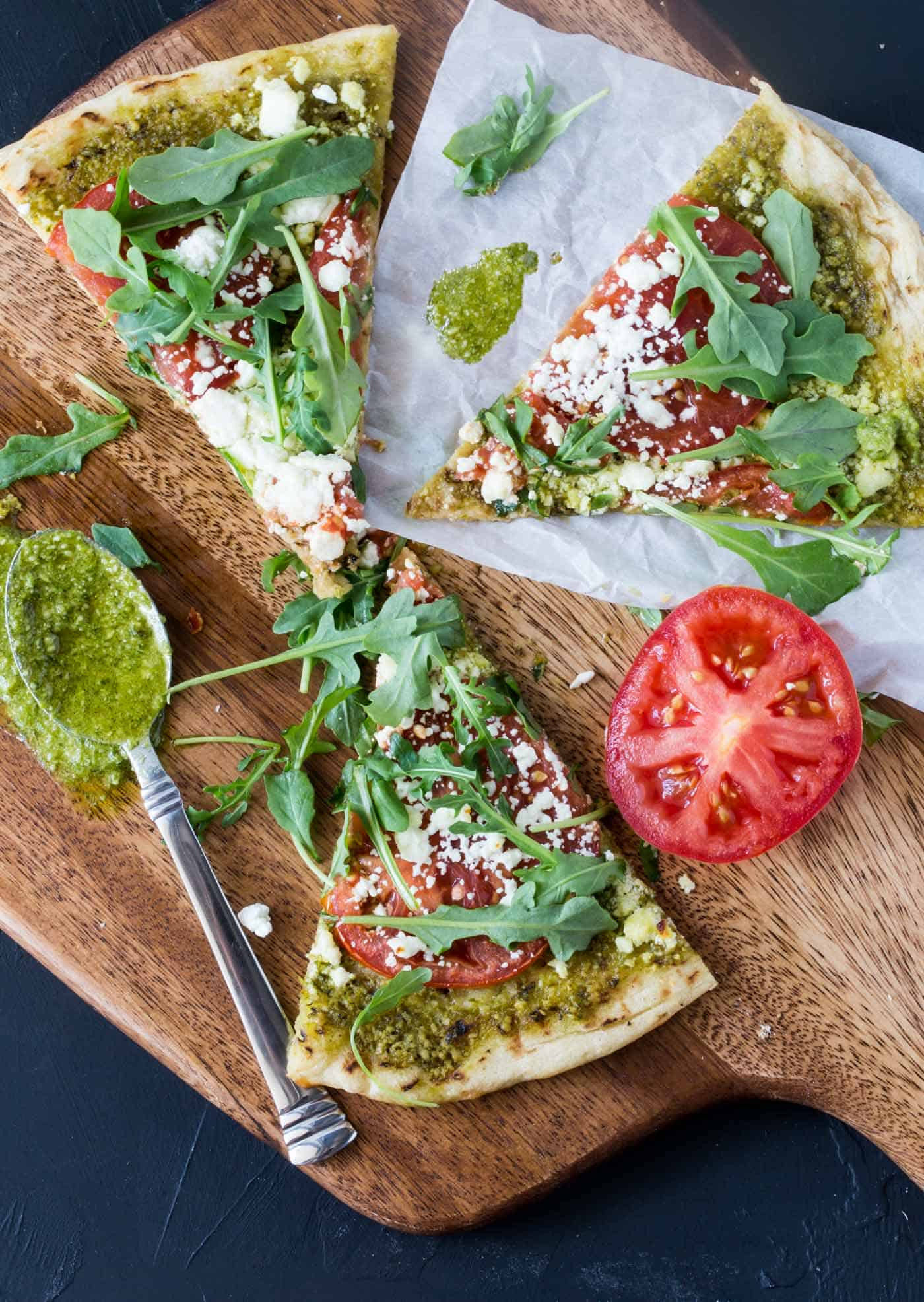 Pesto Pizza with Goat Cheese, Tomatoes and Arugula on a wooden cutting board.