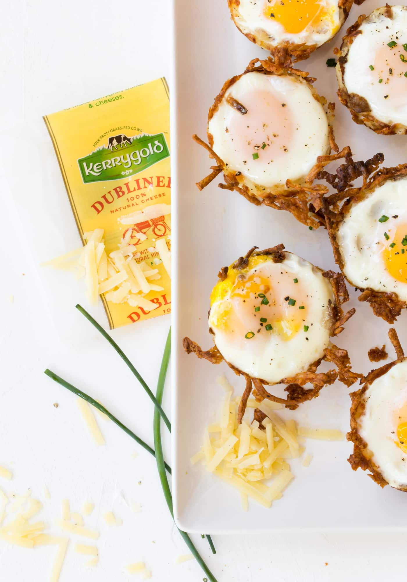 White platter of Sausage, Cheese and Hash Brown Cups. Eggs are baked in the hash brown cups. Garnished with chives and Kerrygold Dubliner Cheese.
