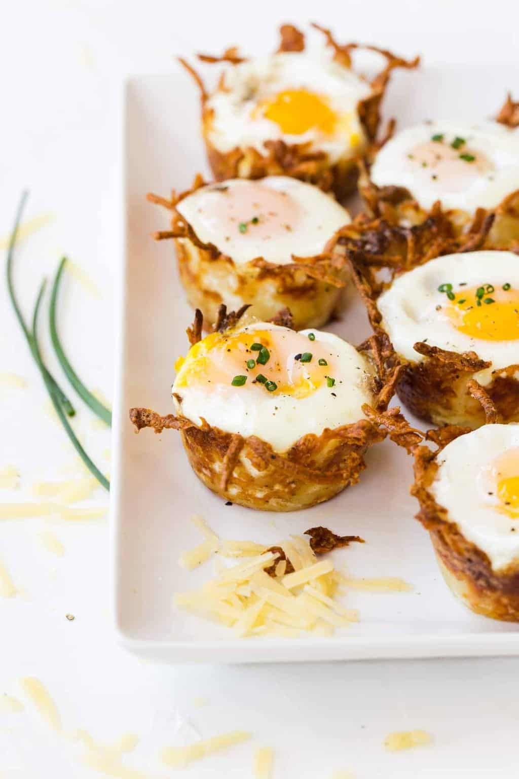 White platter filled with Sausage, Cheese and Hash Brown Cups. Eggs are baked in the hash brown cups. Garnished with shredded cheese and chives.