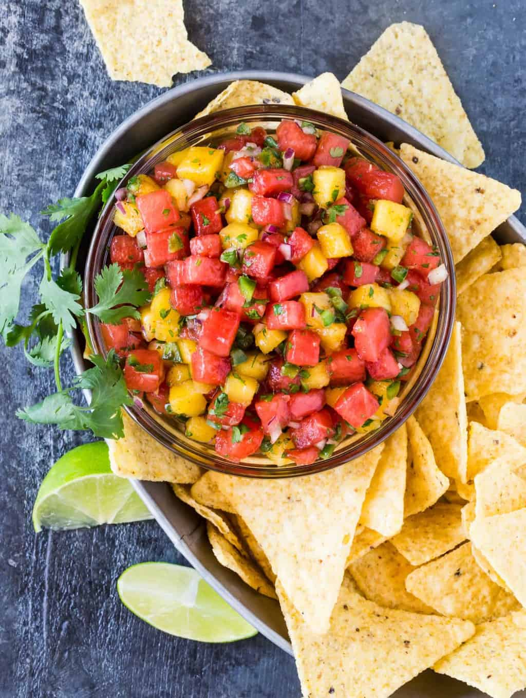 Bowl of watermelon salsa with tortilla chips and lime wedges.