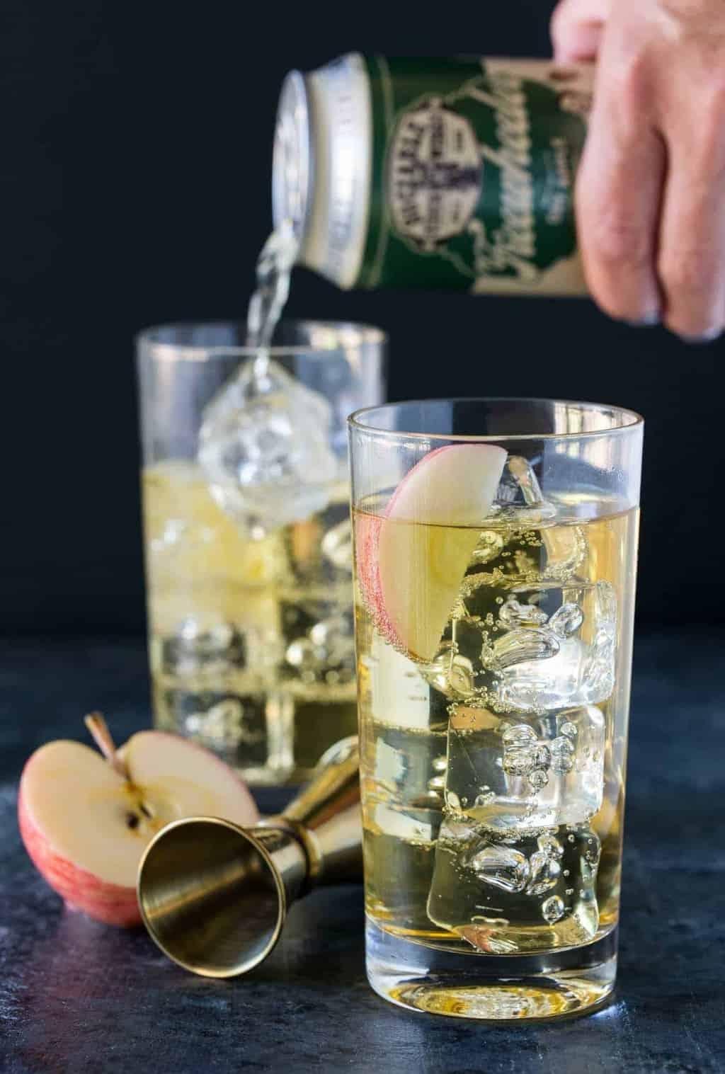 Two ice-filled glasses of Elderflower Hard Cider Cocktails garnished with apple slices.