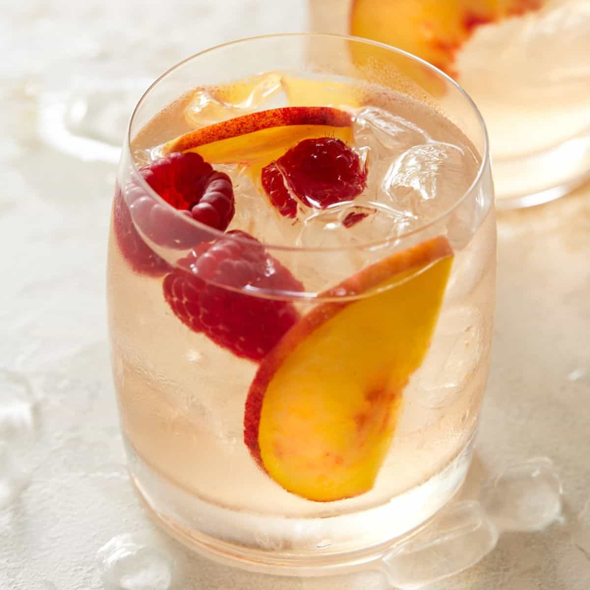 Glass of Rosé Sangria garnished with fresh peach slices and raspberries.