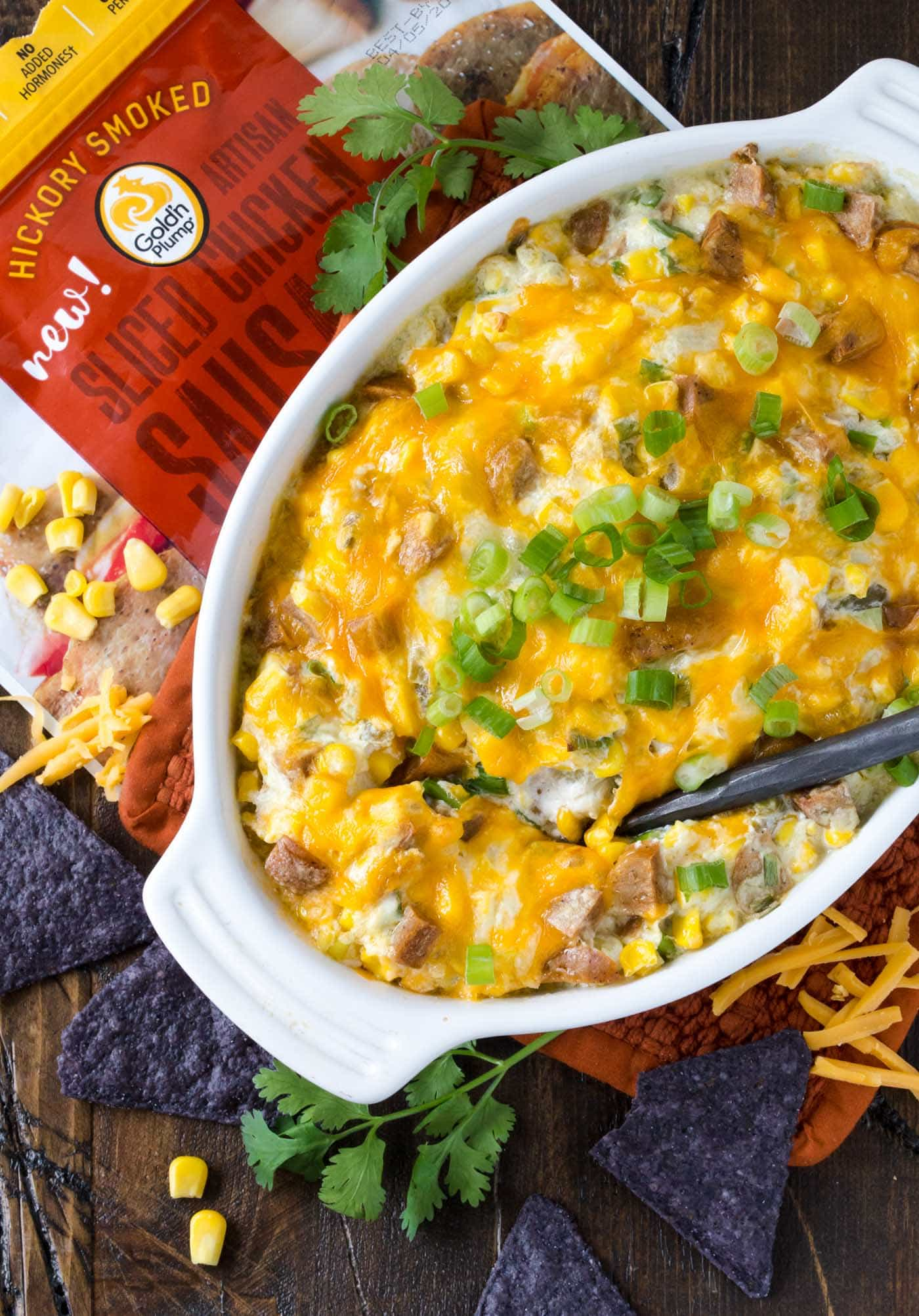 A white casserole dish filled with Zippy Sausage and Corn Dip. Topped with melted cheddar cheese and green onions and surrounded by blue corn tortilla chips.