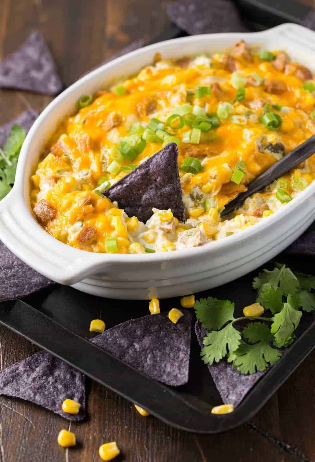White casserole dish filled with Zippy Sausage and Corn Dip from the oven. The dip is topped with melted cheddar cheese and green onions and surrounded by cilantro and corn tortilla chips.