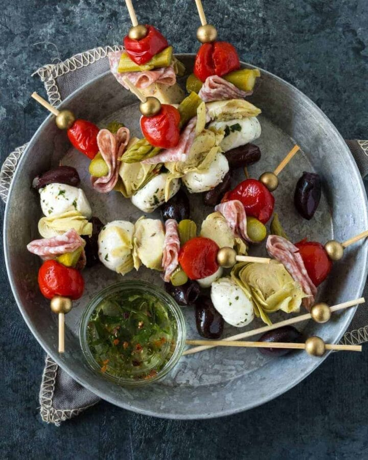 Anitpasto Skewers with peppers, artichoke hearts, mozzarella and salami threaded on skewers with flavored oil for dipping sauce.
