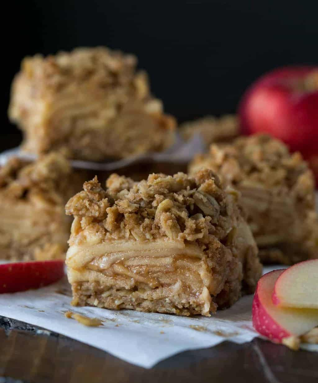 Slices of Apple Crisp Bars with layers of apples, and a crunchy oatmeal crips topping on parchment paper.