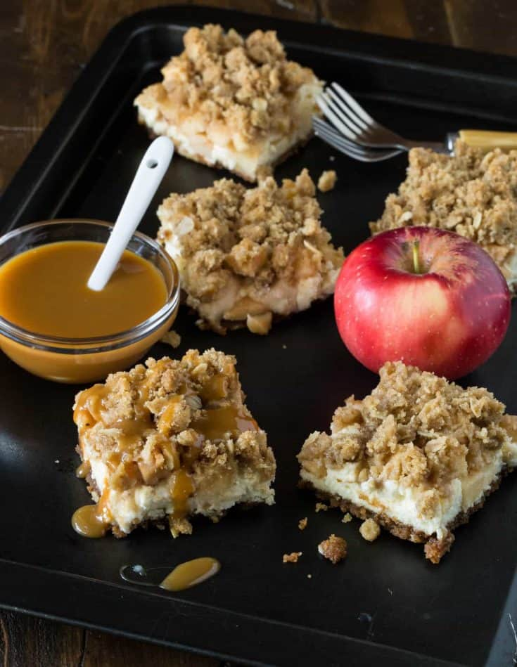 Caramel Apple Cheesecake Bars with Biscoff Cookie Crust on a dark sheet pan. An apple, forks and a bowl of caramel sauce sit beside the bars.