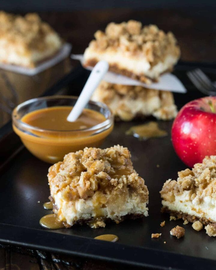 Sheet pan of Caramel Apple Cheesecake Bars with bowl of caramel sauce.