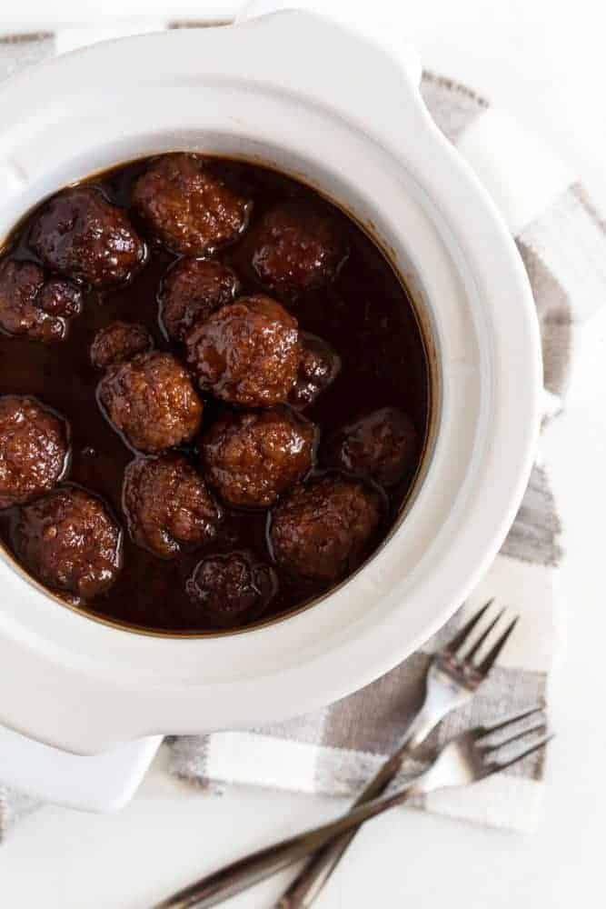 Cocktail size meatballs coated in cherry chipotle barbecue sauce in a small white slow cooker on a white board. Small gray and white check napkin with forks on it in front.