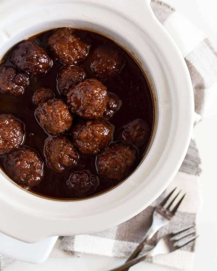 Cocktail size meatballs coated in cherry chipotle barbecue sauce in a small white slow cooker on a white board.