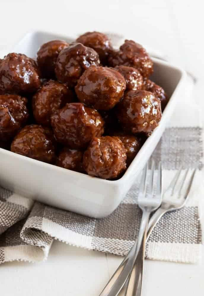 Small white bowl filled with small meatballs coated in cherry chipotle barbecue sauce with cocktail forks to the side placed on a white board.
