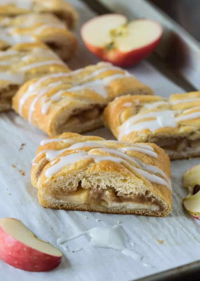 Apple Cream Cheese Danish slices drizzled with a powdered sugar glaze on parchment paper with apple slices.