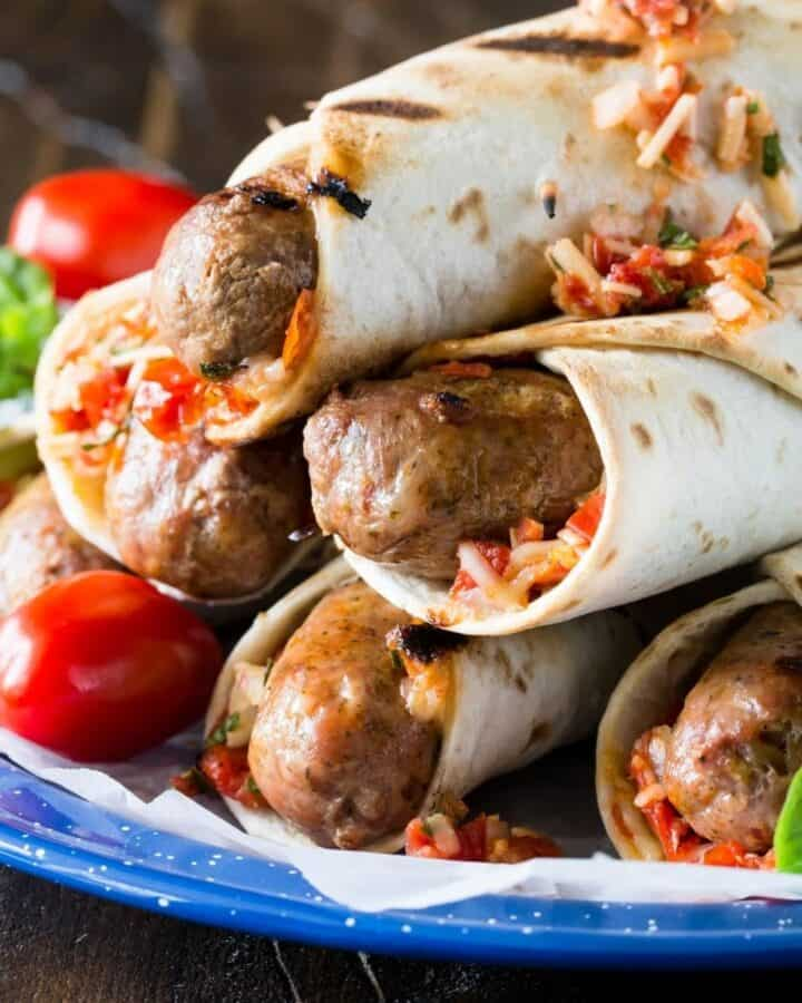 Italian grilled sausage wraps stacked on top of each other in a pyramid.