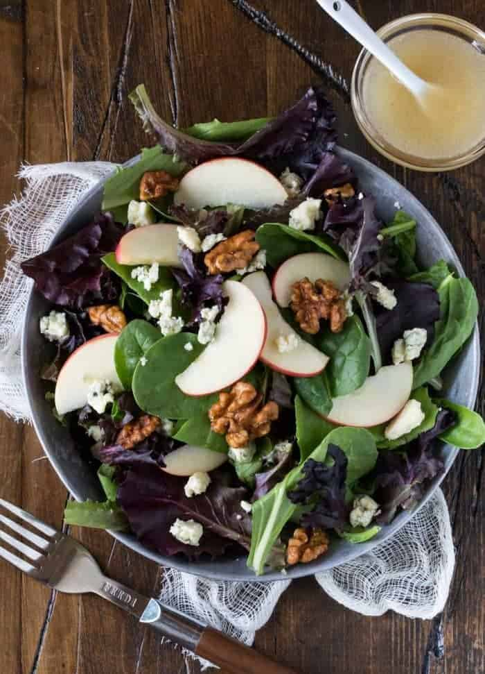 Apple Blue Cheese Walnut Salad on a silver tray garnished with sliced apples. Dressing on side with a fork in foreground.