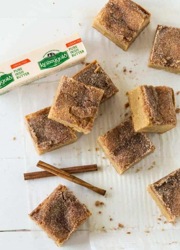 Snickerdoodle Bars cut into squares on a white board with cinnamon sticks for garnish.
