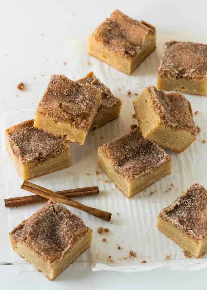 Thick and Chewy Snickerdoodle Bars cut into squares with cinnamon sticks on side.