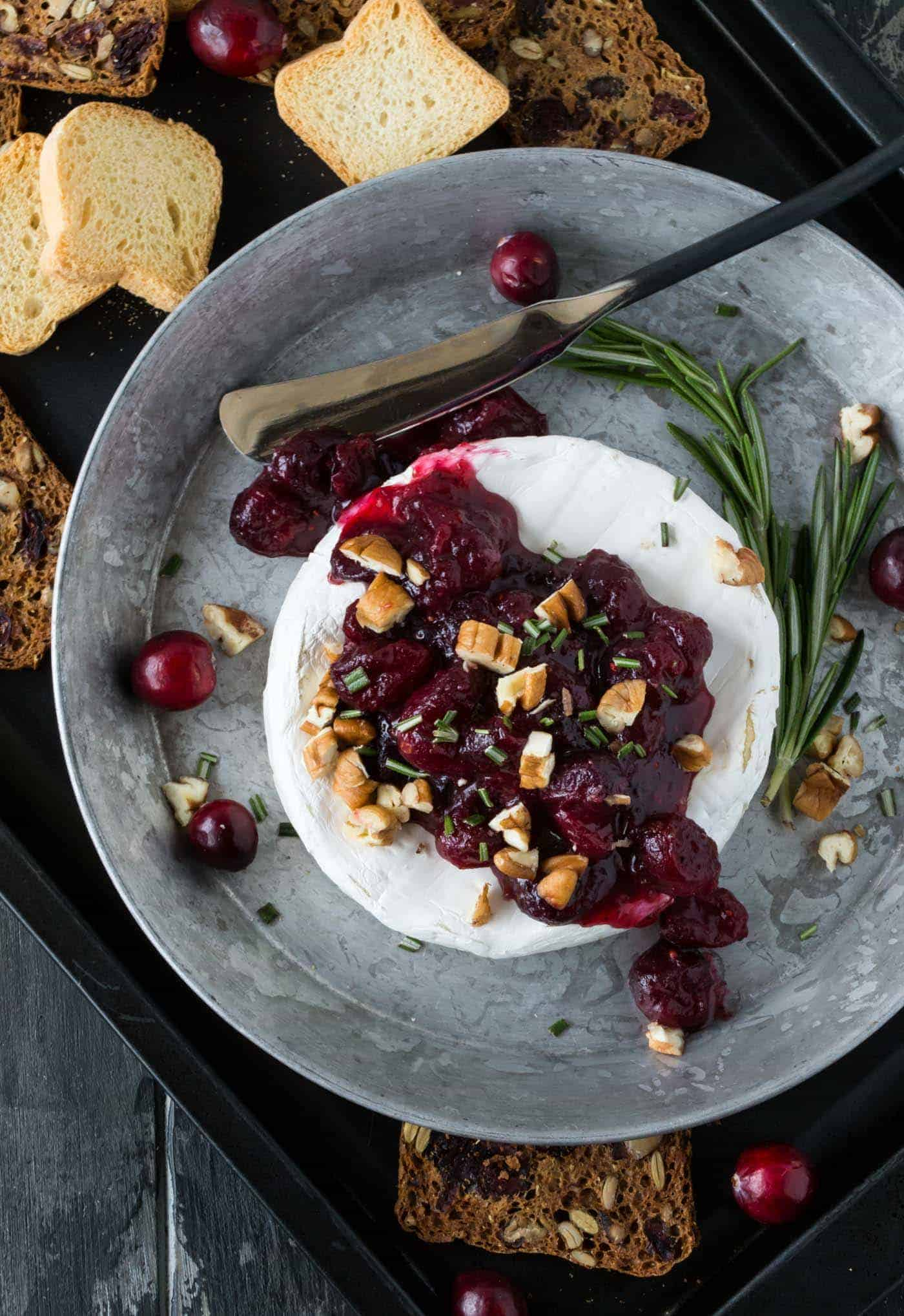 Brie topped with cranberry compote in a silver tray with crackers.