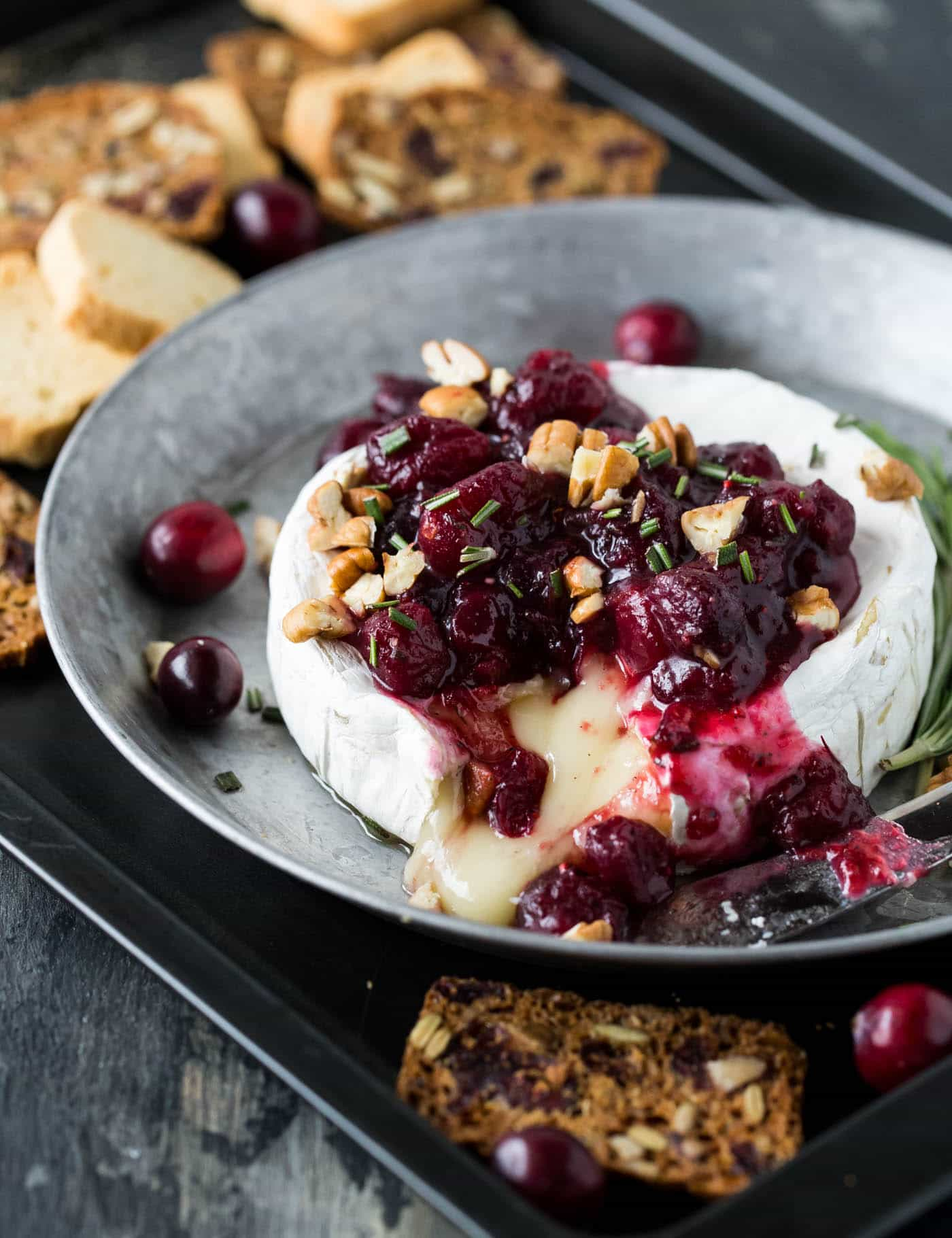 Warm brie topped with cranberries and pecans surrounded by crackers and mini toasts.