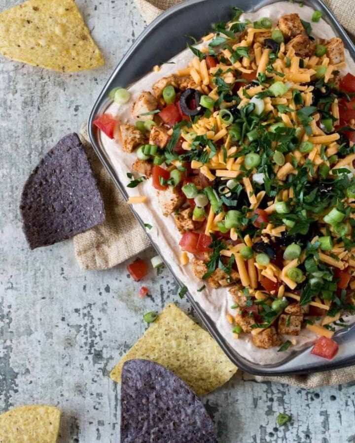 7 Layer Chicken Taco Dip with cheddar cheese, chopped chicken, black olives, diced tomatoes, cheddar cheese and cilantro with tortilla chips for eating.