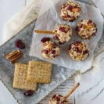 Mini Cranberry Cheddar Cheese balls on parchment paper with mini pretzel sticks for garnish.