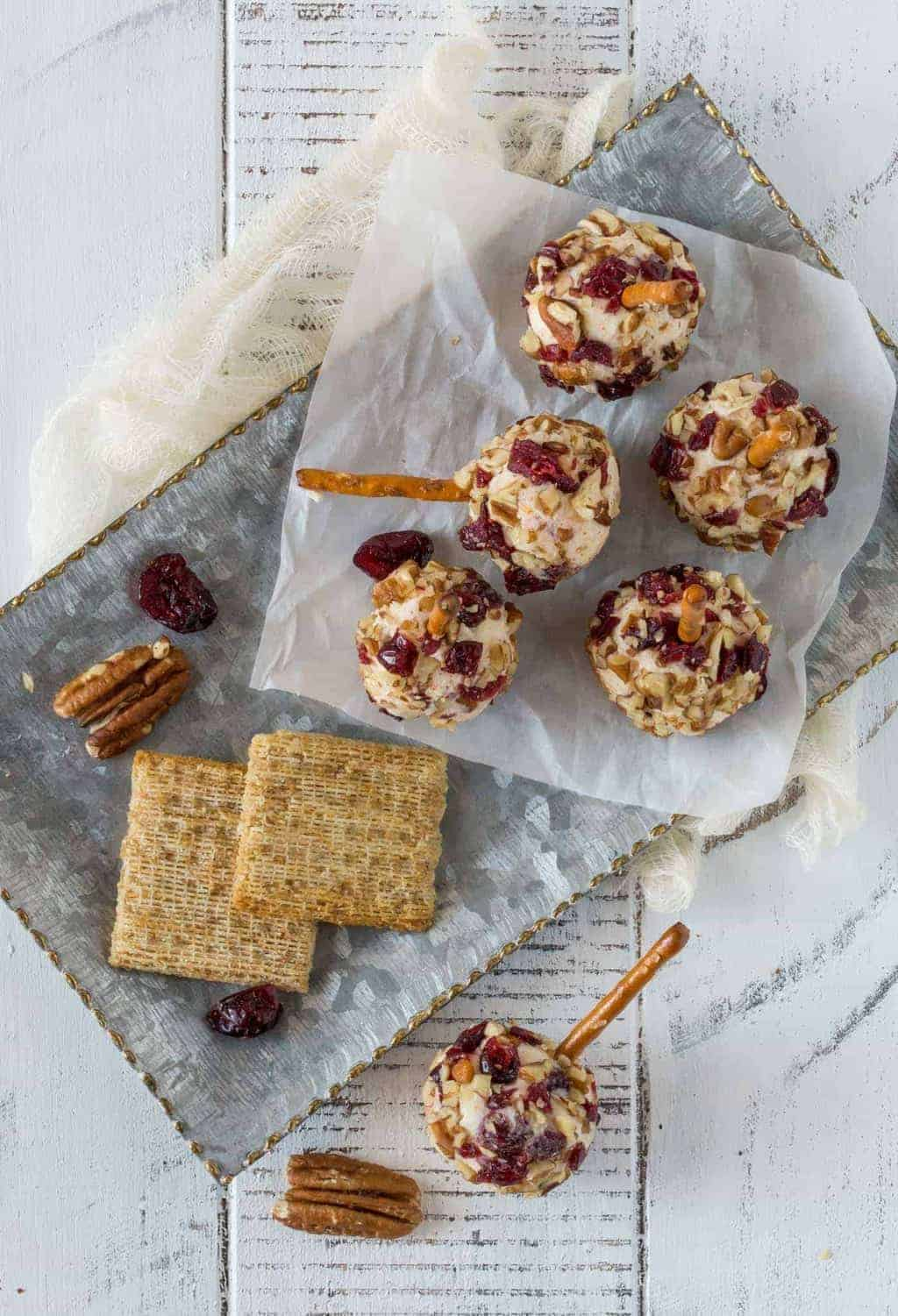 Mini Cranberry Cheddar Cheese balls on parchment paper with mini pretzel sticks for garnish.