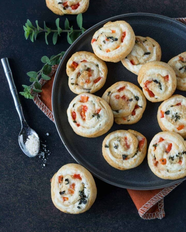 parmesan pinwheels piled on grey plate. Small spoon with parmesan cheese and oregano for garnishes on a dark background.