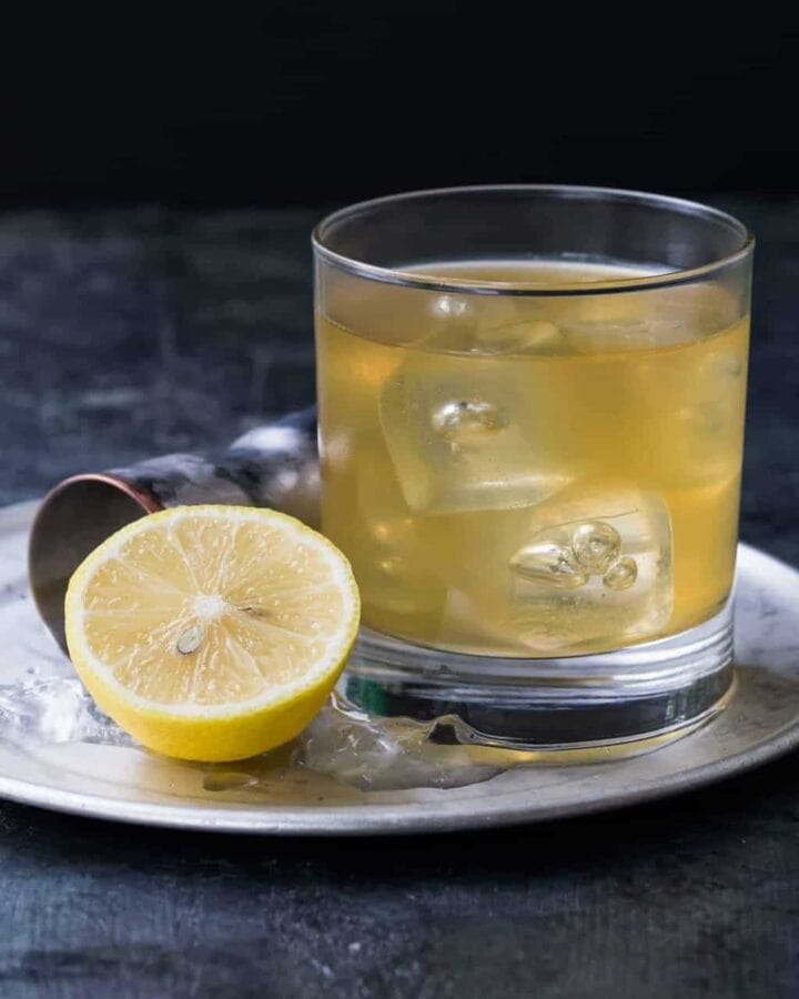 A Gold Rush Cocktail in a low ball glass on a silver tray. The cocktail is made with bourbon, ginger liqueur and fresh lemon juice.