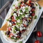 Layered Greek Dip on a white platter with a bowl of toasted pita chips.