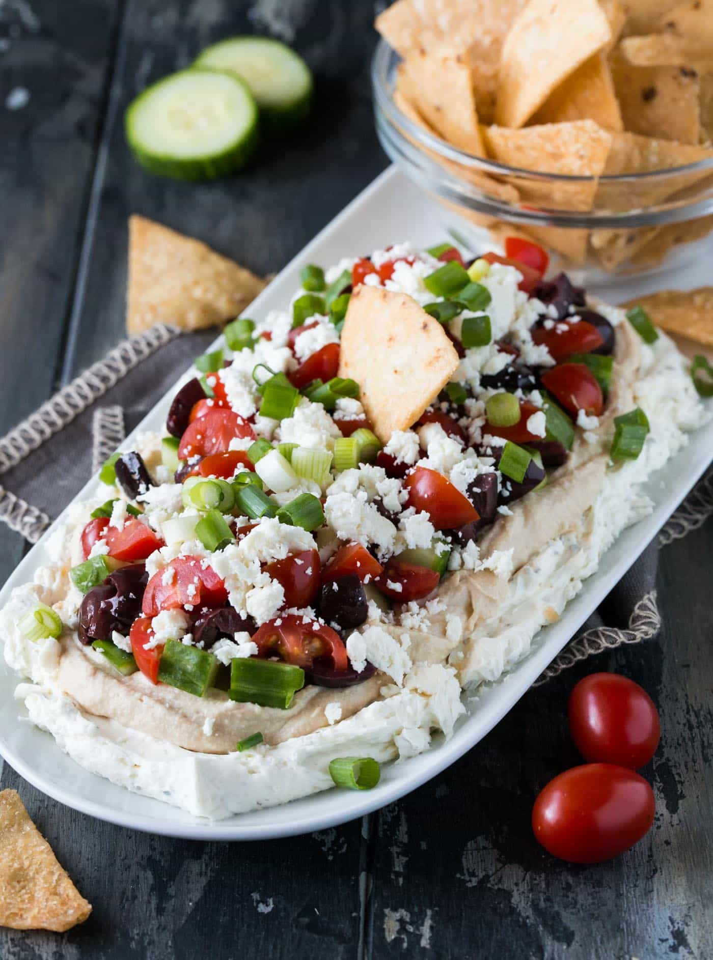 Layered Greek Dip on a white platter with a bowl of baked pita chips.