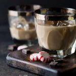 Two glasses of Mint Chocolate Irish Cream Cocktails on a dark wooden board. Garnished with peppermint candies and dark chocolate chunks.