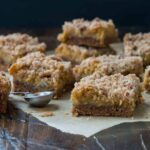 Pumpkin Butter Bars with a cinnamon pecan streusel topping layered on a piece of parchment paper on top of a wooden board