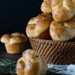 Woven basket filled with homemade Rosemary Garlic Cloverleaf Rolls on black background. Sprig of fresh rosemary is near the basket.