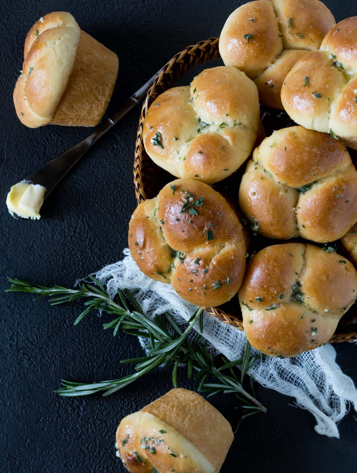 Top down view of a woven basket filled with homemade Rosemary Garlic Cloverleaf Rolls. Two rolls are next to the basket along with a butter knife with a pat of butter.