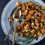 Silver plate filled with Rosemary Roasted Sweet Potatoes and Onions and garnished with sprigs of fresh rosemary.