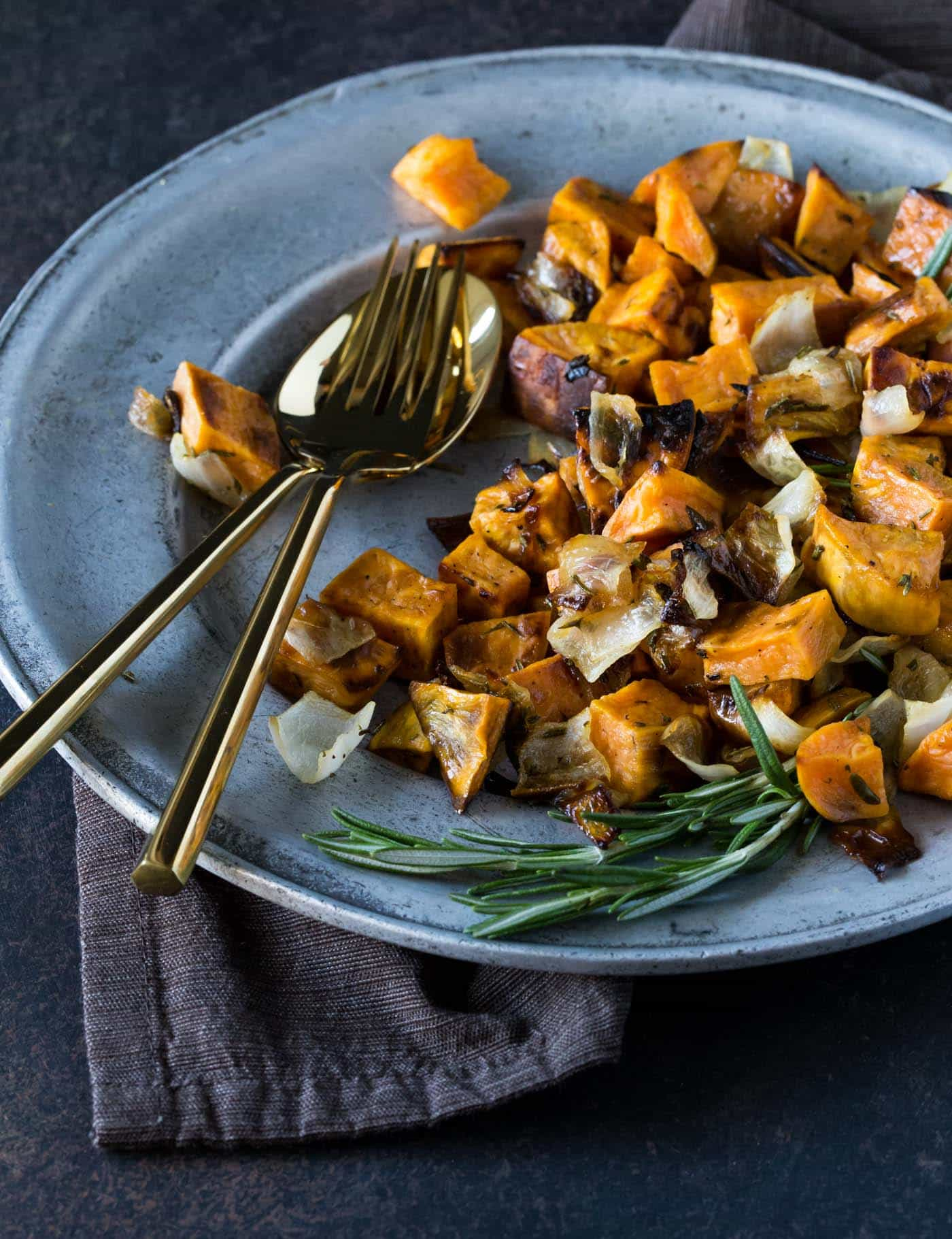 A silver plate filled with Rosemary Roasted Sweet Potatoes and Onions. Gold serveware and fresh rosemary sprigs are nearby.