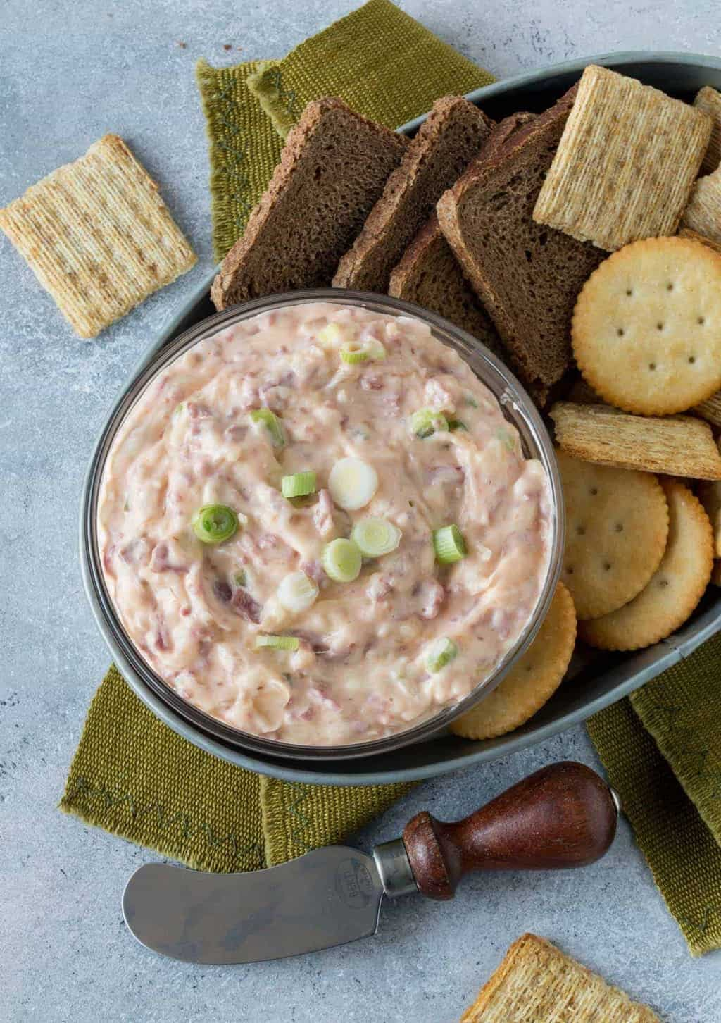Creamy Reuben Dip is a small glass bowl with crackers and cocktail bread for serving.
