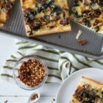 Multiple squares of Spinach, Caramelized Onion and Bacon Sheet Pan Pizza with a small bowl of crushed red pepper flakes.